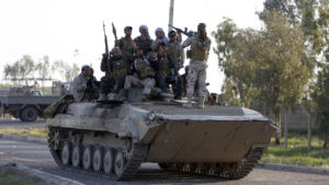 Iraqi security forces and Shi'ite fighters pose on a tank in the Salahuddin province March 2, 2015. Iraq's armed forces, backed by Shi'ite militia, attacked Islamic State strongholds north of Baghdad on Monday as they launched an offensive to retake the city of Tikrit and the surrounding Sunni Muslim province of Salahuddin.     REUTERS/Thaier Al-Sudani (IRAQ - Tags: POLITICS CONFLICT CIVIL UNREST) - RTR4RTII